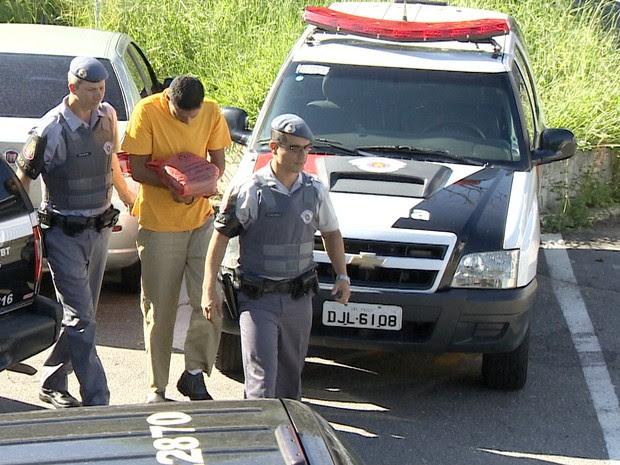 Policial militar chega escoltado até a sede da Delegacia de Investigações Gerais de Taubaté. (Foto: Reprodução/TV Vanguarda)
