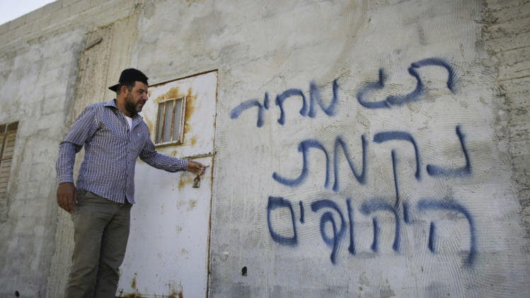 "A Palestinian stands outside a house with Hebrew graffiti that reads, ""price tag"" after Palestinians reported Jewish settlers had burned a house in Aqraba village, near the West Bank city of Nablus, Wednesday, July 2, 2014. A tiny fringe group of radical Israeli settlers have been carrying out acts of vandalism in recent years to protest what they perceive as the Israeli government's pro-Palestinian policies and in retaliation for Palestinian attacks. The vandals have targeted mosques, churches, dovish Israeli groups and even Israeli military bases in these so-called ""price tag"" assaults. (AP Photo/Nasser Ishtayeh)"