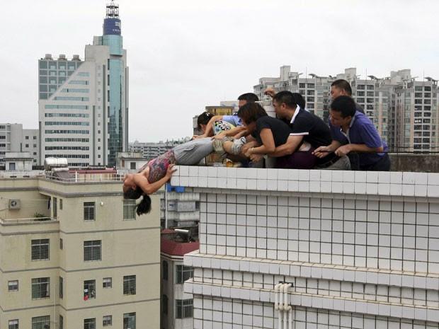 Familiares se aproximaram e tentaram retirá-la do topo do edifício (Foto: Reuters)