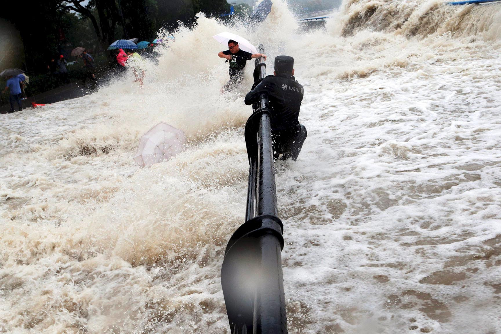 A paramilitary policeman holds onto a fence as tourists dodge tidal waves increased under the influence of Typhoon Dujuan, at the bank of Qiantang river, in Hangzhou