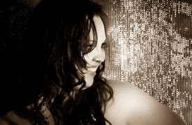 A black and white photo of Aidy looking sideways, face half covered by her tumble of hair with a disco bright background