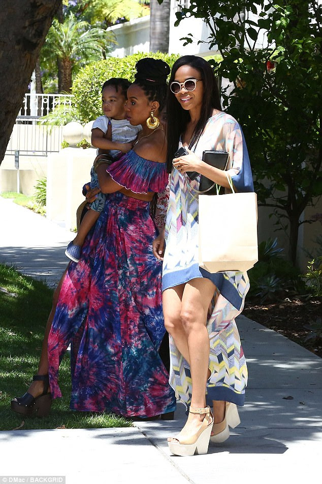 Aglow: Meanwhile, Michelle wore a springtime chic multicolored print dress with a blue-fringed hem that stopped at mid-thigh in the front but at the back was ankle-length