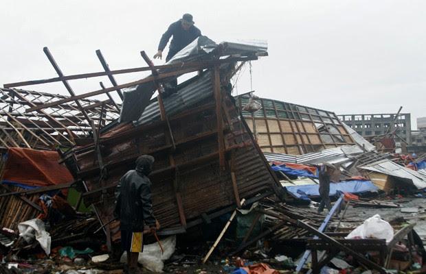homem é visto no topo de uma casa destruída em Tacloban, após passagem do tufão nas Filipinas (Foto: AFP)