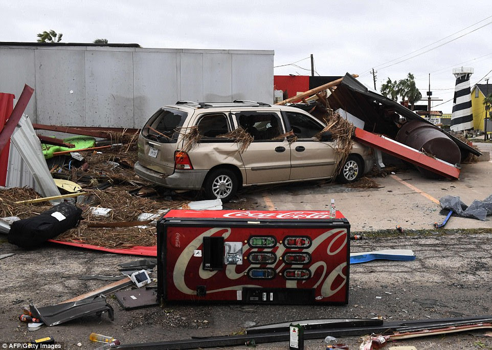 A knocked over soda machine lies in front of a damaged car and ravaged main street in Port Aransas, one of the worst hit areas