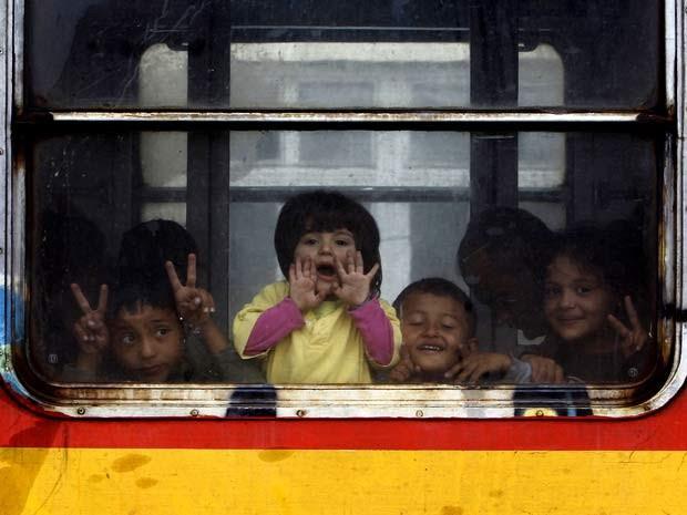 Crianças acenam de dentro de trem que os levará da Macedônia para a Sérvia (Foto: AP Foto/Boris Grdanoski)