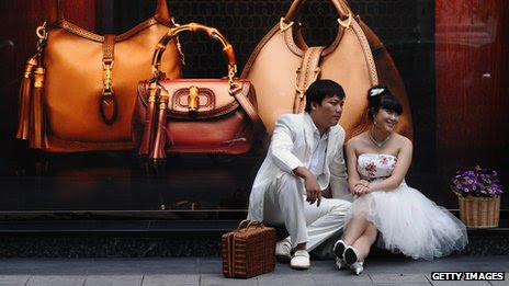 A young couple sit in front of a Gucci shop in Vietnam