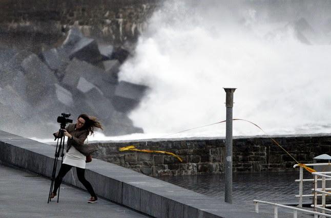 Una dona lluita amb el vent a tocar de la platja de La Zurriola de Sant Sebastià