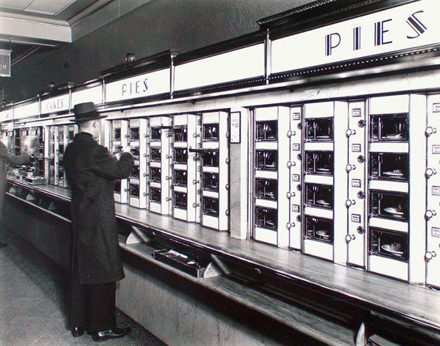 Automat, 977 Eighth Avenue, Manhattan. Man takes pie out of Automat, stone counters and walls below metal and glass display.