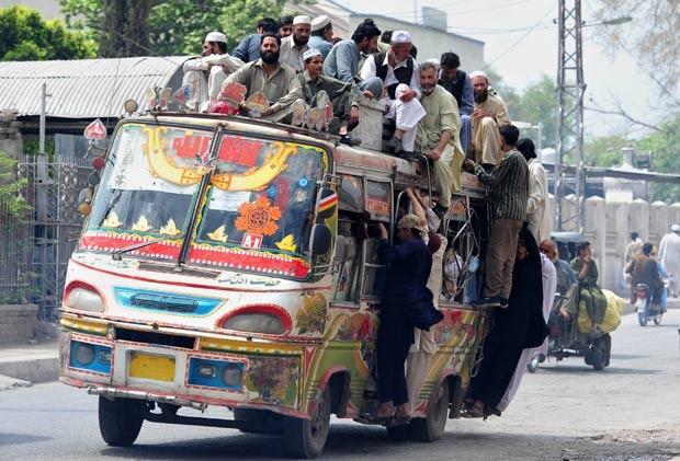 Em 10 de abril de 2012, um ônibus foi flagrado superlotado em Peshawar, no Paquistão. Em cima do teto, viajavam pelo menos 15 pessoas. Outras estavam agarradas às laterais do ônibus. (Foto: A. Majeed/AFP)