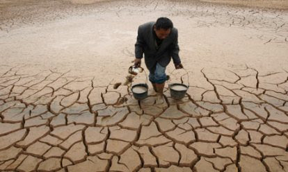 A farmer takes water from a dried-up pond to water his vegetable field during a drought in Jiangxi province. Photograph: Stringer Shanghai/Reuters (Courtesy of guardian.co.uk)