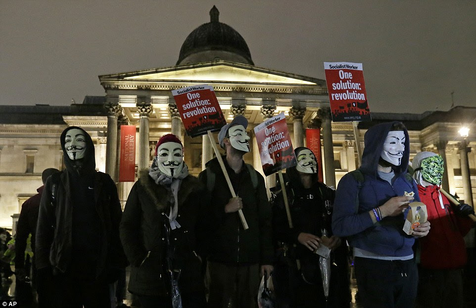 Demonstrations: Campaigners wearing sinister Guy Fawkes masks - made famous in the film V for Vendetta - gathered in Trafalgar Square
