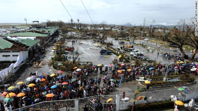 People queue up to receive relief goods being distributed at Tacloban's airport on November 10, 2013.