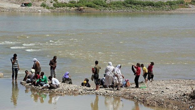 Yazidis wash themselves in the Tigris River at Fishkhabour, northern Iraq on 10 August 2014