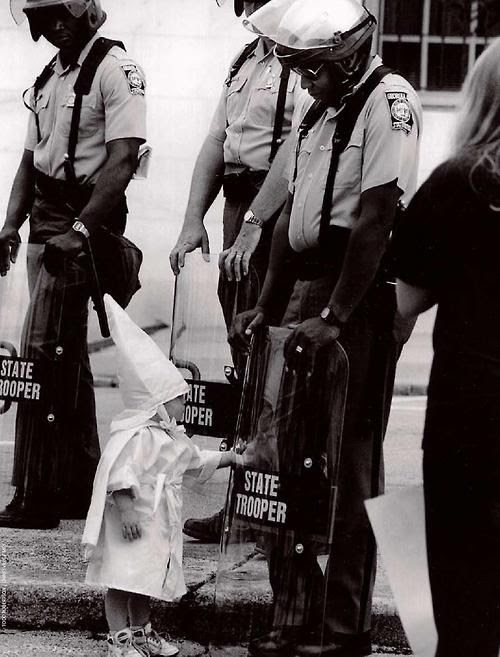 Child of a KKK member is innocently curious about a black police officer. (1992)