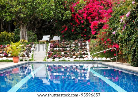 Blue Water In A Small Hotel Swimming Pool Reflect Various Colorful ...