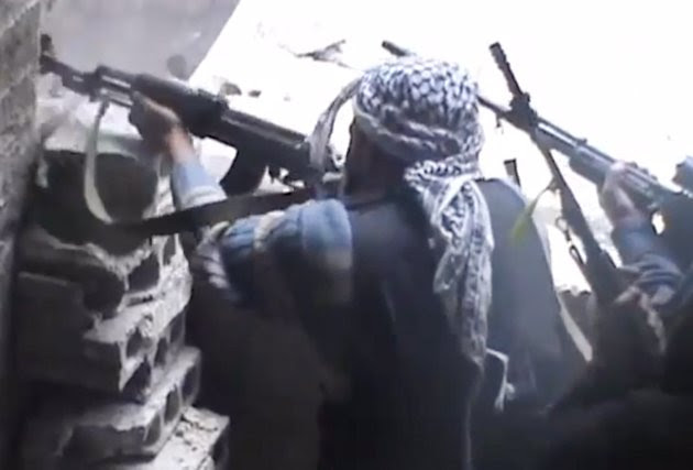 In this image taken from video obtained from the Ugarit News, which has been authenticated based on its contents and other AP reporting, Free Syrian Army fighters aim their weapons during clashes, in Damascus countryside, Syria on Monday, March 25, 2013. (AP Photo/Ugarit News via AP video)