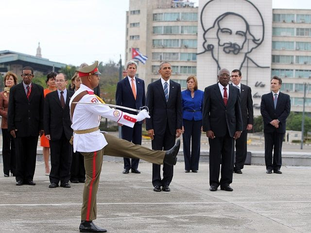 """U.S. President Barack Obama, center, and Secretary of State John Kerry, center left, stand as an honor guard marches during a ceremony at the Jose Marti monument in Revolution Square in Havana, Cuba, Monday, March 21, 2016. Third from right is Salvador Valdes Mesa Vice-President of Cuba's State Council. """"It is a great honor to pay tribute to Jose Marti, who gave his life for independence of his homeland. His passion for liberty, freedom, and self-determination lives on in the Cuban people today,"""" Obama wrote in dark ink in the book after he laid a wreath and toured a memorial dedicated to the memory of Jose Marti. (AP Photo/Enric Marti)"""