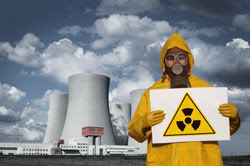 Man in radiation suit outside nuclear powerplant