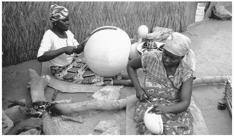 Women engrave designs into yellow calabash gourds. Nigerian art traditionally served a social or religious purpose.