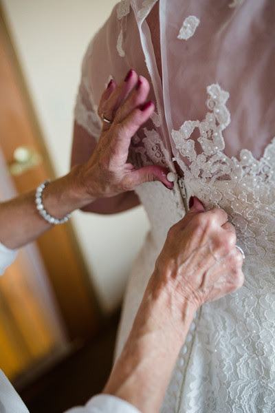 The Bride puts on her dress with her Mother at the Country Inn and Suites in Sycamore IL for her wedding at Blumen Gardens.