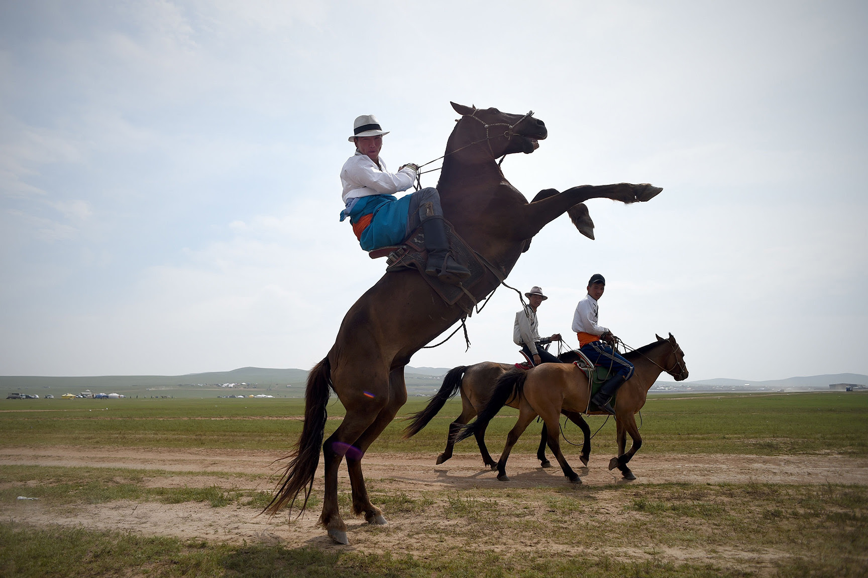 A Mongolian man controls his horse