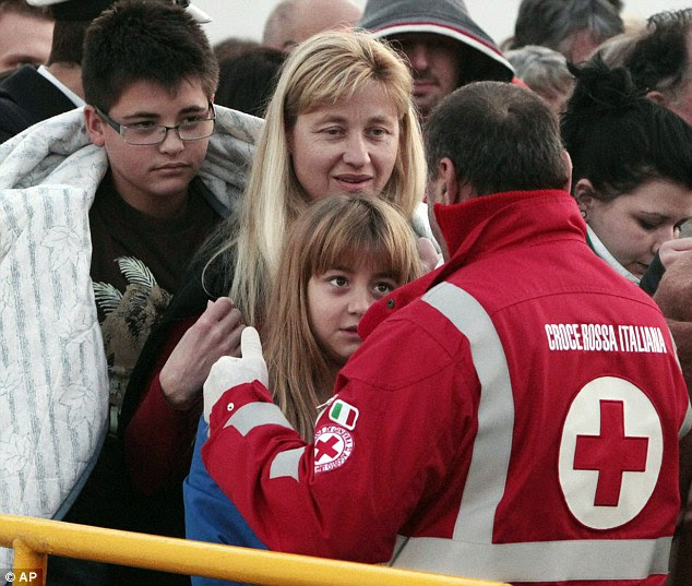 Three passengers huddle in blankets as they arrive on a ferry in Porto Santo Stefano. Twenty-four Britons were onboard