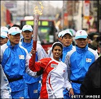 Konnie Huq carries the torch surrounded by Chinese security guards