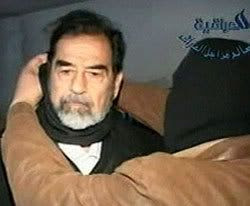 Saddam Hussein getting his hood removed by an executioner.