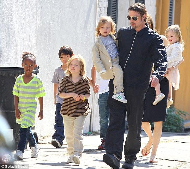 A família: Shiloh caminha ao lado de seu pai como o clã amble através de uma das suas cidades preferidas, Nova Orleans, em março