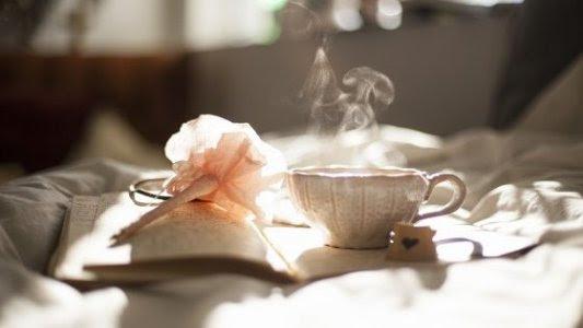 Taza de té sobre un libro con una flor de papel.