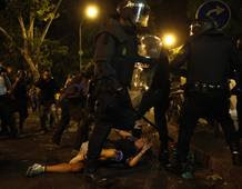 Protester reacts as riot police surround him outside Spanish parliament in Madrid