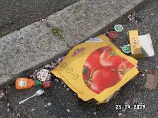 a discarded Pizza box and trimmings in the kerbside
