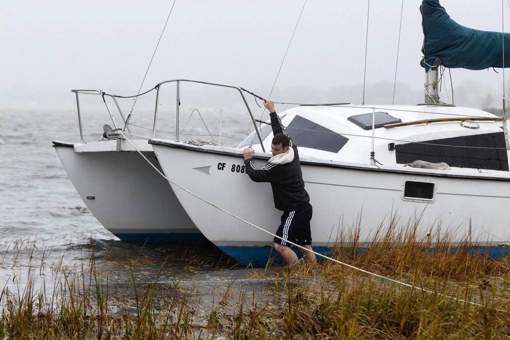 A man struggles to secure his boat near a marsh after breaking off its mooring and beaching itself during the effects of Hurricane Sandy in Quincy, Massachusetts. The monster storm bearing down on the East Coast, strengthened on Monday after hundreds of thousands moved to higher ground.