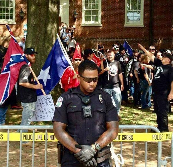 As Neo-Nazi scumbags march behind him, an African-American police officer does his duty providing protection for this filth that it doesn't deserve.