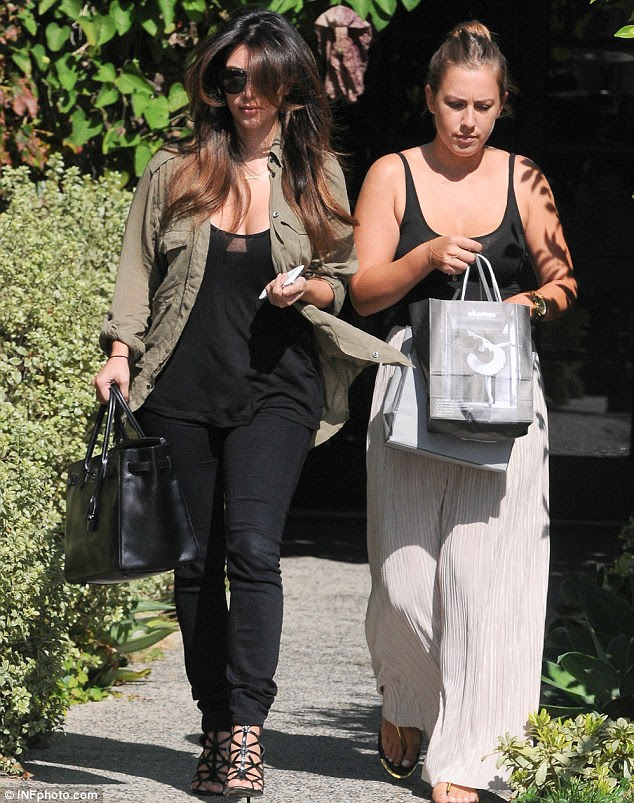 Walking? Kim runs errands with an assistant in Beverly Hills yesterday; she has just treated herself to a new offroad vehicle