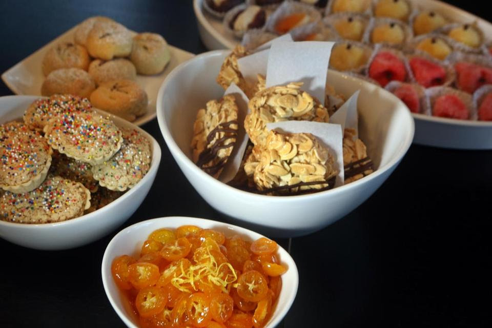 A Mimouna spread with cookies, marzipan sweets, and a bowl of kumquat slices.