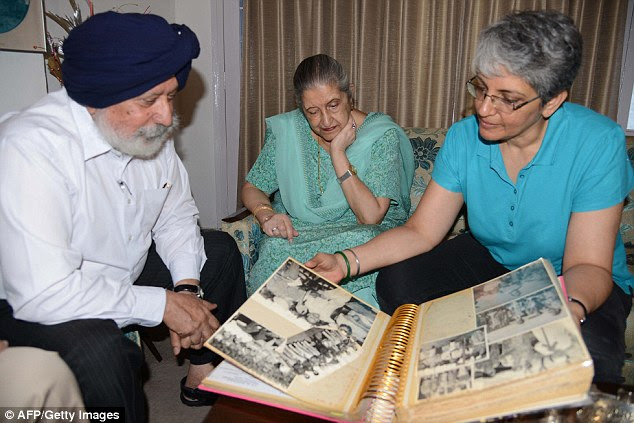 Reminiscing: Ms Kaur looks on as her daughter Gurveen and lawyer Manjit Singh Khaira leaf through old photograph albums filled with pictures of her late father