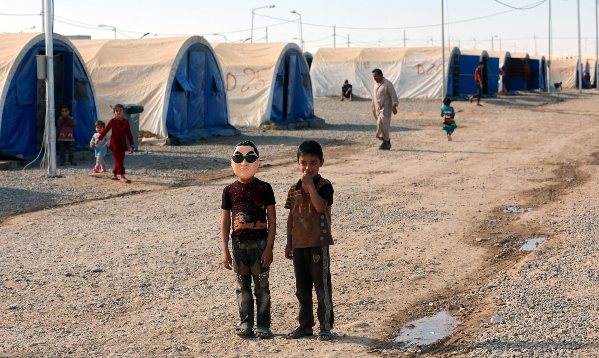 An Iraqi displaced boy (L) wears a mask depicting Korean pop star Park Jae-sang as he stands with a friend at Jadaa refugees camp near Qayyarah city, some 40 km southern Mosul, Iraq, 17 November 2016. According to a local official in Jadaa camp, the camp which was opened after the beginning of the military operation to liberation of Mosul city, is currently hosting around ten thousand people who fled from many villages near Mosul due to the fighting between the Iraqi forces and Islamic State (IS) group.  EPA/AHMED JALIL
