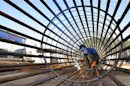 A worker welds steel bars at a construction site for a new train station in Ningbo