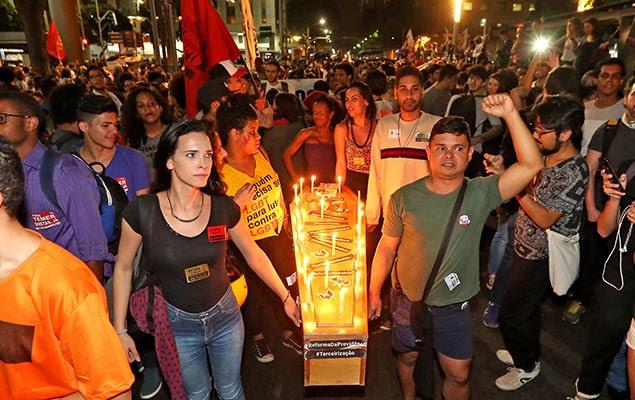 """***EMBARGADA PARA USO EM INTERNET*** RIO DE JANEIRO, RJ, 18.05.2017: TEMER-PROTESTOS - Manifestantes da Frente Povo Sem Medo já se concentram em frente à igreja da Candelária, na avenida Presidente Vargas, no centro do Rio. Eles ocupam toda a praça em frente à igreja. Há bandeiras da CUT, PC do B, PCB e CTB. Em cartazes e camisetas, pedem """"Diretas já"""". (Foto: Marco Antonio Teixeira/UOL/Folhapress)"""