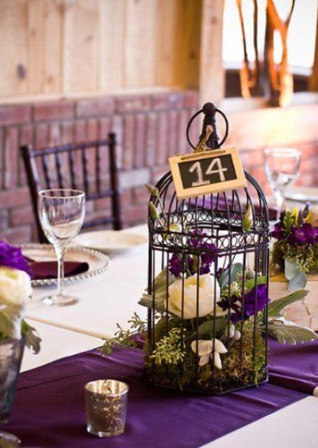 eine dunkle Vogelkäfig mit lila und weißen Blumen und Moos für eine mutige Hochzeit, eine Tafel-Tabelle Anzahl