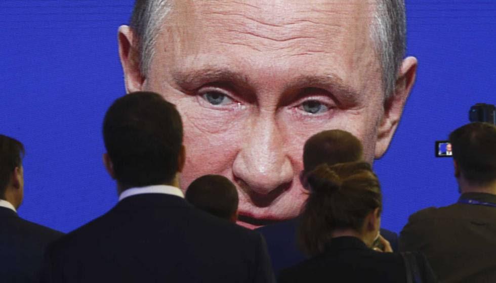 Asistentes del Foro Económico Internacional de San Petersburgo el 2 de junio frente a una pantalla donde aparece el presidente de Rusia, Vladímir Putin.