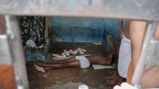 Homem deitado apenas de cueca em chão úmido e sujo em Pedrinhas