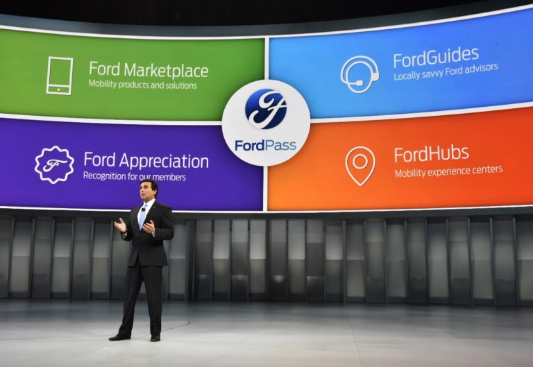 Ford CEO Mark Fields standing in front of large curved screen showing images of Ford Pass