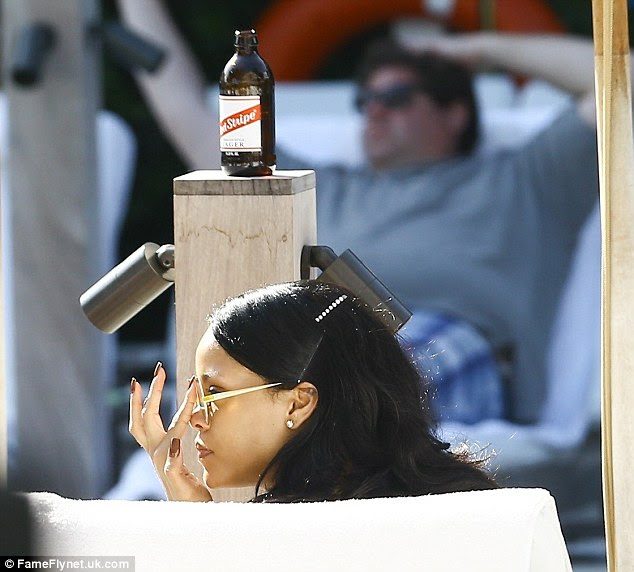 Hitting the spot: RiRi relaxed poolside in a lounge chair as a Jamaican beer stood on a counter in front of her
