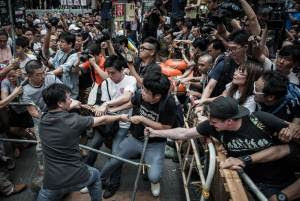 Pro-democracy protesters (R) protect a barricade from…