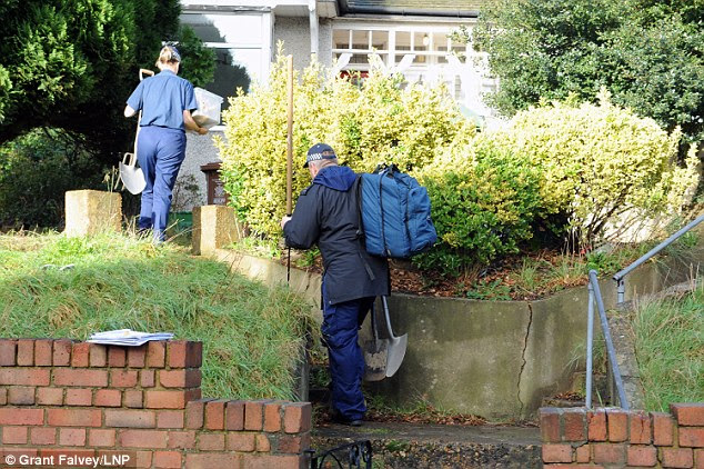Search: Police carrying spades and other digging equipment enter the house as the search for Ms Blake, her husband and two young children continue