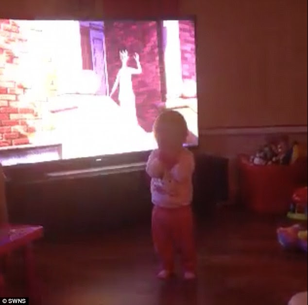 Peek-a-boo: The home video shows Lexi, seen with her hands over her face, playing with her parents
