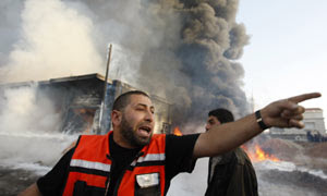 A Palestinian firefighter shouts following an Israel air strike in Gaza Strip