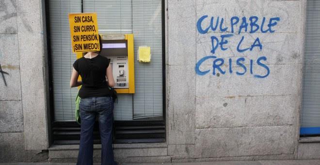 Una participante en una manifestación contra la austeridad, en un cajero automático en Madrid. REUTERS